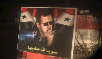 A picture taken through a window of a bus carrying Syrian civilians and rebel-fighters from the town of Douma shows a poster of President Bashar al-Assad at a checkpoint in the city of Tartus, on April 2, 2018