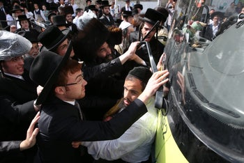 Ultra-Orthodox protesters block Jerusalem roads in demonstration over a police decision to perform an autopsy on a dead baby.