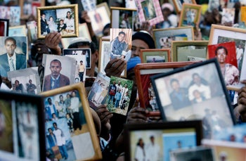 Ethiopian immigrants hold up photographs of their relatives during a demonstration