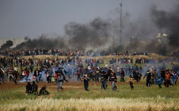 Teargas canisters fired by Israeli troops falls down at Palestinians during a demonstration near the Gaza Strip border with Israel, in eastern Gaza City, March 30, 2018.