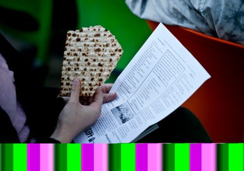 A participant in the 'Freedom Seder' holds a matza and the revised text of the Haggaddah read at the event.