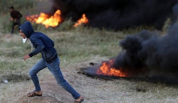 Palestinian protester runs for cover during a protest at the border between Israel and Gaza on April 4, 2018.