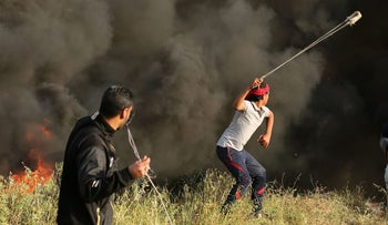 Palestinian protesters using slingshots to throw stones during clashes with Israeli troops east of Gaza City on April 4, 2018.