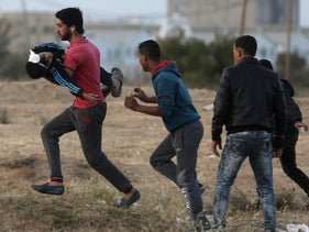 A Palestinian protester evacuates a wounded boy during a protest at Gaza's border with Israel on April 4, 2018.