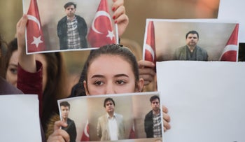 Students of Mehmet Akif College hold pictures of their Turkish teachers as they demonstrate against their arrest in Pristina on March 29, 2018.