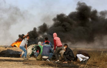 Palestinian protesters cover during clashes with Israeli troops along Gaza's border with Israel, east of Khan Younis, Gaza Strip, Thursday, April 5, 2018