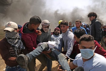 Palestinian men carry an injured protester after clashes with Israeli forces at the Israel-Gaza border, April 6, 2018.