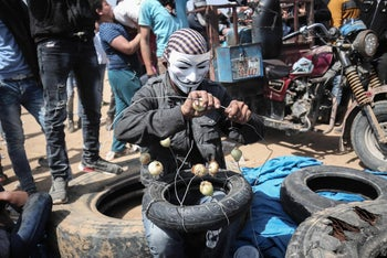 A Palestinian man wearing an Anonymous mask prepares to protest with onions to the effects of tear gas at the Israel-Gaza border, April 6, 2018.