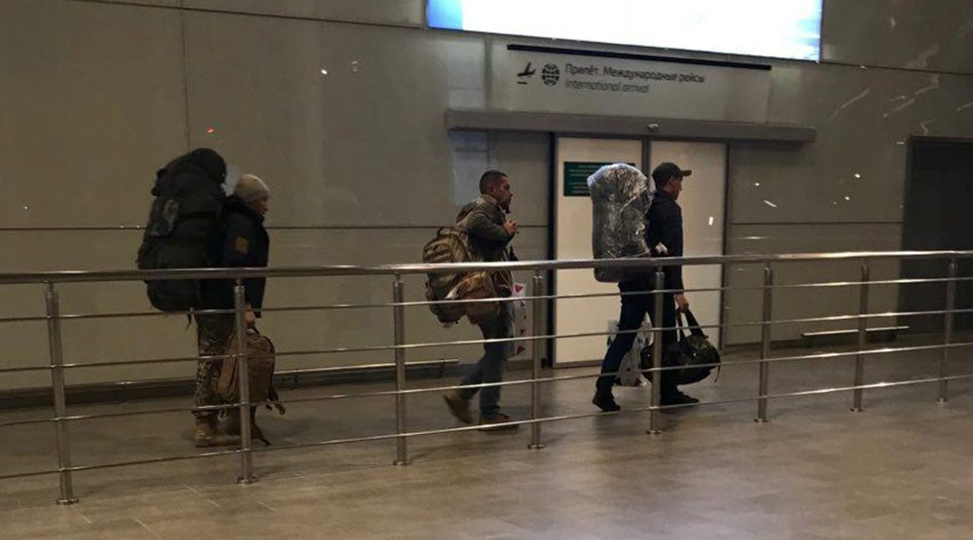Unidentified men carrying camouflage rucksacks and Damascus Airport duty-free bags arrive from Syria at Rostov Airport in Russia, January 26, 2018.