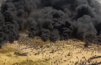 A drone photo shows smoke rising as Palestinian protesters burn tires during a demonstration near the Gaza border, April 6, 2018.