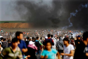 Palestinians protest as Israeli forces fire tear gas on the Israel-Gaza border, April 6, 2018.