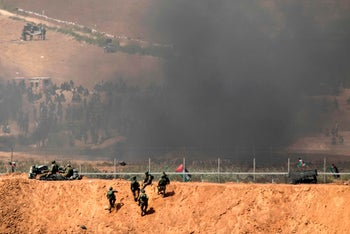 Smoke from burning tires between Palestinian protesters and Israeli soldiers, April 6, 2018.