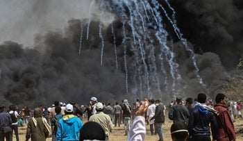 Tear gas fired by Israeli forces passes through smoke created by Palestinian protesters burning tires during clashes along the Gaza-Israel border on April 6, 2018.