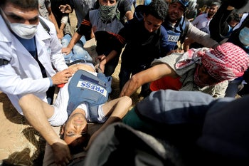 Mortally wounded Palestinian journalist Yasser Murtaja, 31, is evacuated during clashes with Israeli troops at the Israel-Gaza border, in the southern Gaza Strip  April 6, 2018