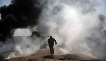 A Palestinian protester runs for cover from teargas fired by Israeli troops during a protest at the Gaza Strip's border with Israel, Friday, April 6, 2018