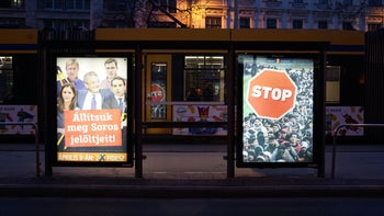"""""""Stop the Soros candidate"""" next to a """"stop"""" (migration) campaign poster in Budapest, Hungary."""