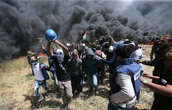 Palestinians evacuate mortally wounded Palestinian journalist Yasser Murtaja, 31, during clashes with Israeli troops at the Israel-Gaza border
