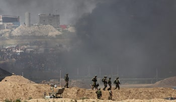 Israeli security forces seen as smoke from burning tires billows over the Gaza border fence on April 6, 2018