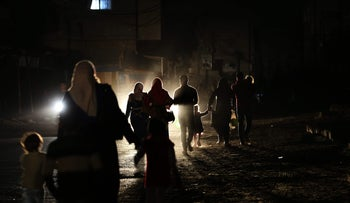 FILE PHOTO: Palestinians walk on a road during a power cut in Gaza Strip, April 14, 2017.