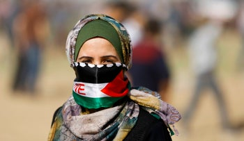 A Palestinian demonstrator covers her face with the colors of the Palestinian flag during clashes with Israeli security forces following a protest on the Gaza-Israel border east of Gaza City. April 6, 2018