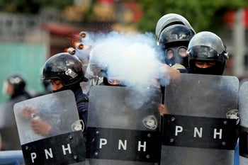 A police officer fires tear gas during clashes with demonstrators as Honduran President Juan Orlando Hernandez is sworn in for a new term in Tegucigalpa, Honduras, January 27, 2018.