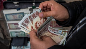 File photo: A currency trader counts Iranian rial banknotes at a money exchange market on Ferdowsi street in Tehran, Iran.