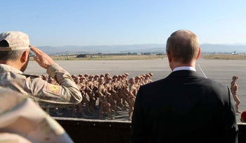 FILE PHOTO: Russian President Vladimir Putin watches the troops marching as he and Syrian President Bashar Assad visit the Hemeimeem air base in Syria, December 12, 2017.