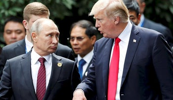 U.S. President Donald Trump and Russia's President Vladimir Putin talk during the family photo session at the APEC Summit in Danang, Vietnam, November 11, 2017