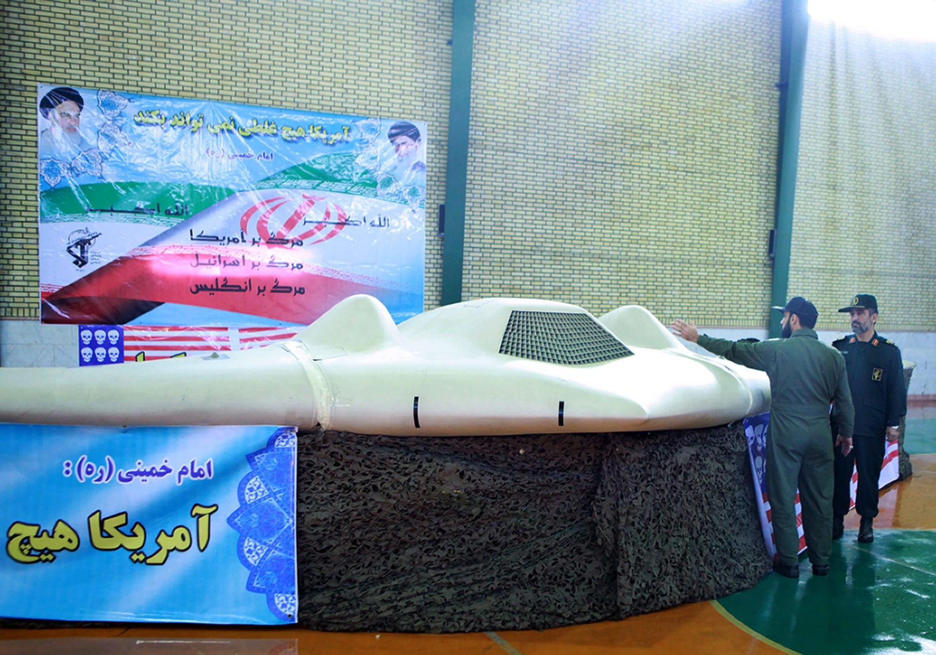 Brigadier General Amir-Ali Hajizadeh looking at what Iranian officials claim is the US RQ-170 Sentinel high-altitude reconnaissance drone that crashed in Iran on December 4, 2011