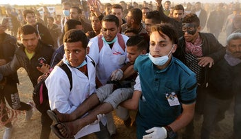 A wounded Palestinian demonstrator is evacuated at the Israel-Gaza border at a protest in the southern Gaza Strip April 9, 2018