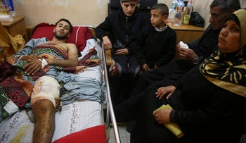 Raed Jadallah, a Palestinian 25-year-old surfer, lies on a bed as his father, mother and brothers visit him, at the Shifa hospital in Gaza, April 9, 2018.