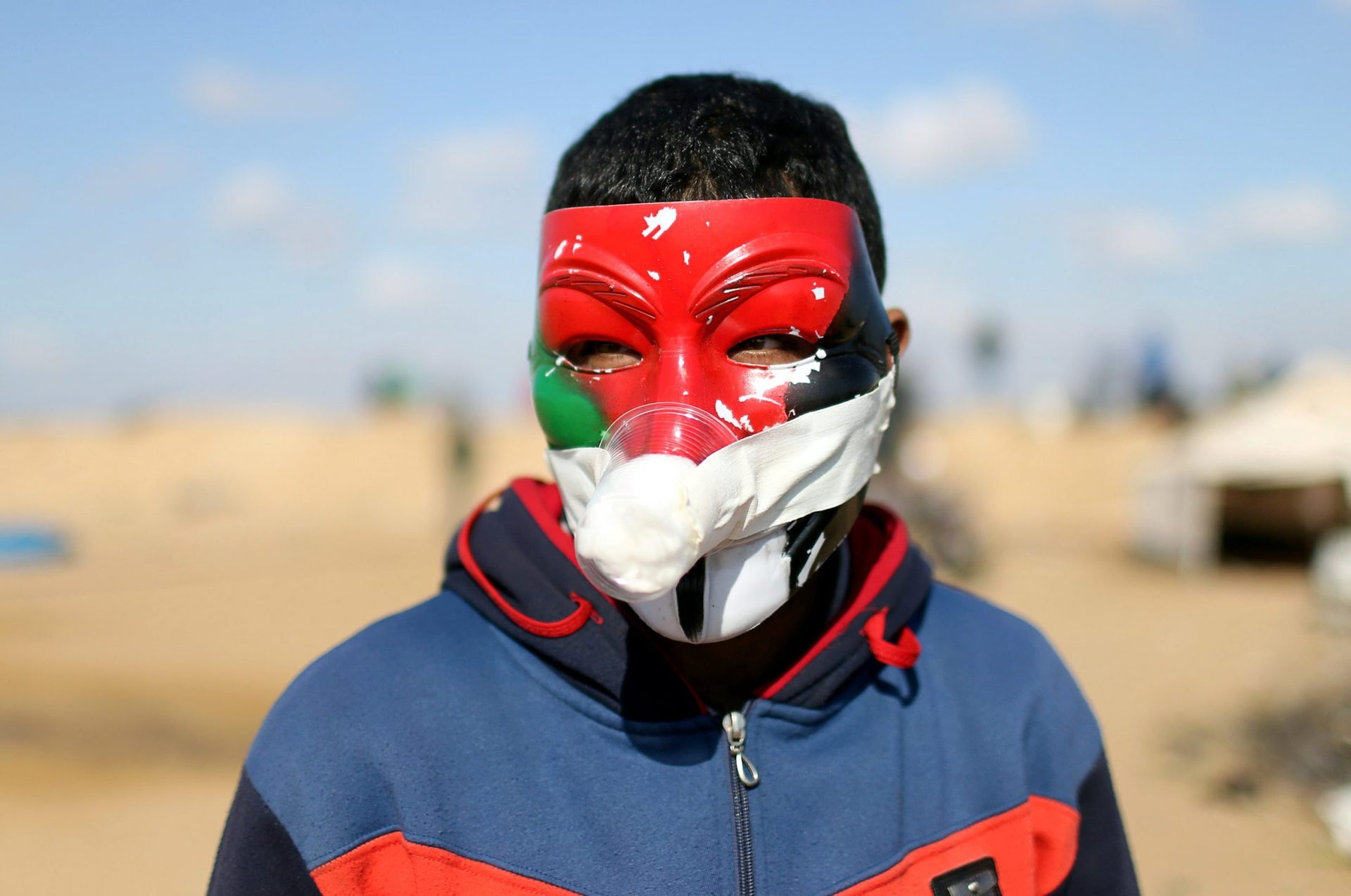 A Palestinian demonstrator wearing a mask covers his nose with a plastic cup filled with perfume and cotton to protect himself from inhaling tear gas fired by Israeli troops during a protest at the Israel-Gaza border in the southern Gaza Strip April 10, 2018. Picture taken April 10, 2018.