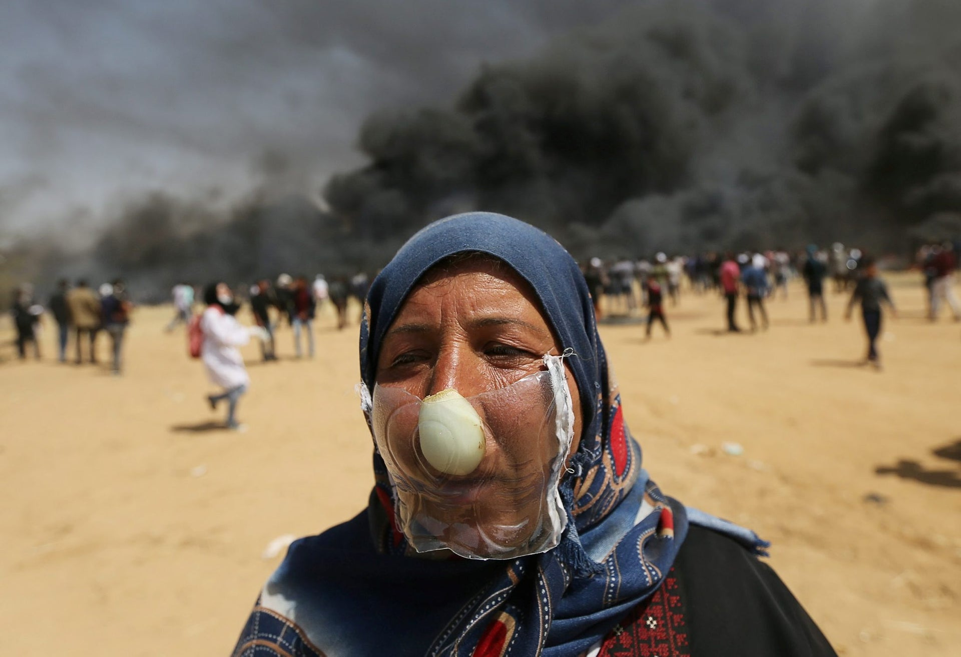 Palestinian woman Jehad Abu Mehsen covers her nose with a piece of plastic and an onion to protect herself from inhaling tear gas fired by Israeli troops during a protest at the Israel-Gaza border in the southern Gaza Strip April 6, 2018. Picture taken April 6, 2018.