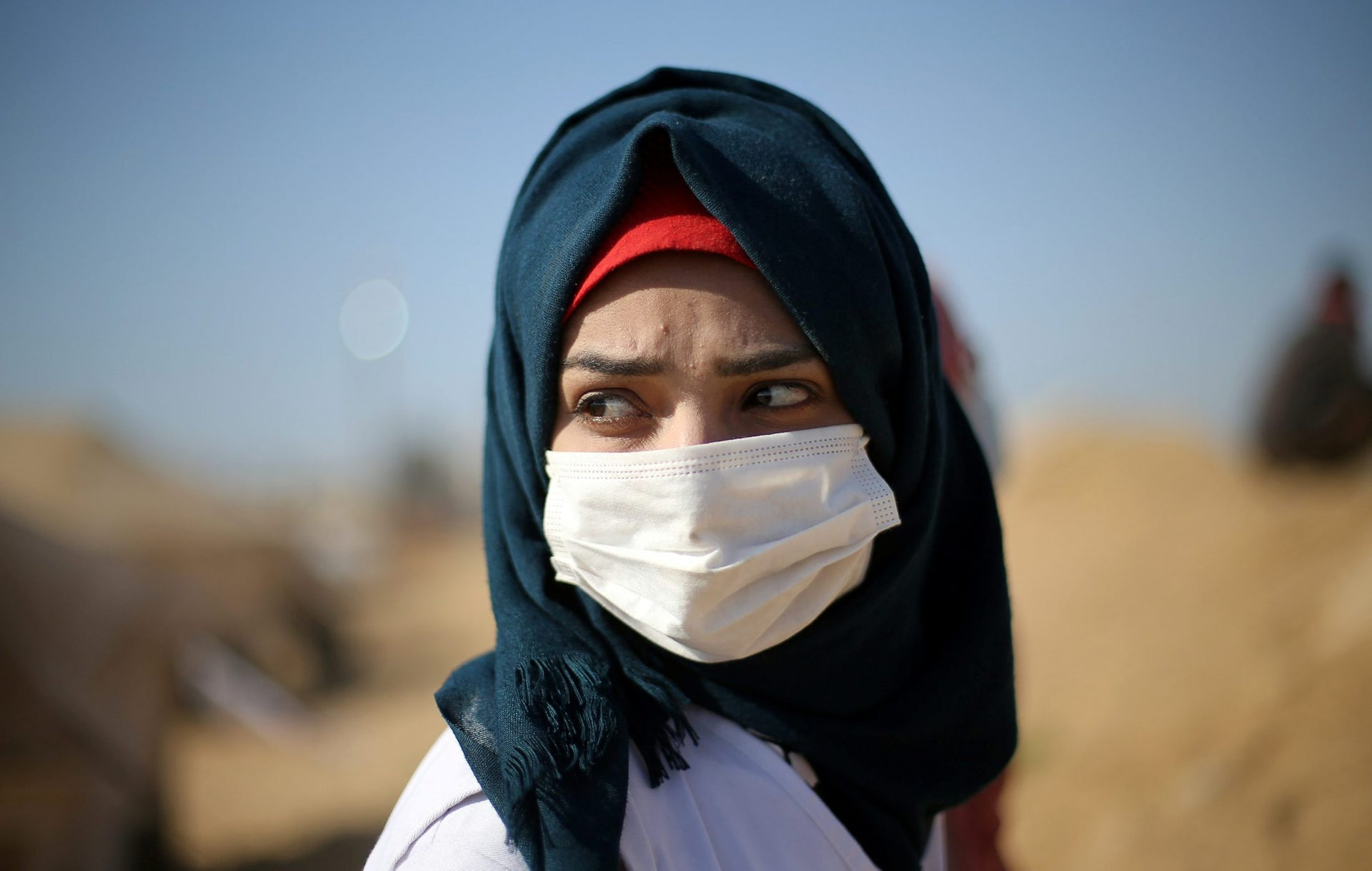 A Palestinian medic wears a mask to protect herself from inhaling tear gas fired by Israeli troops during a protest at the Israel-Gaza border in the southern Gaza Strip April 9, 2018. Picture taken April 9, 2018.