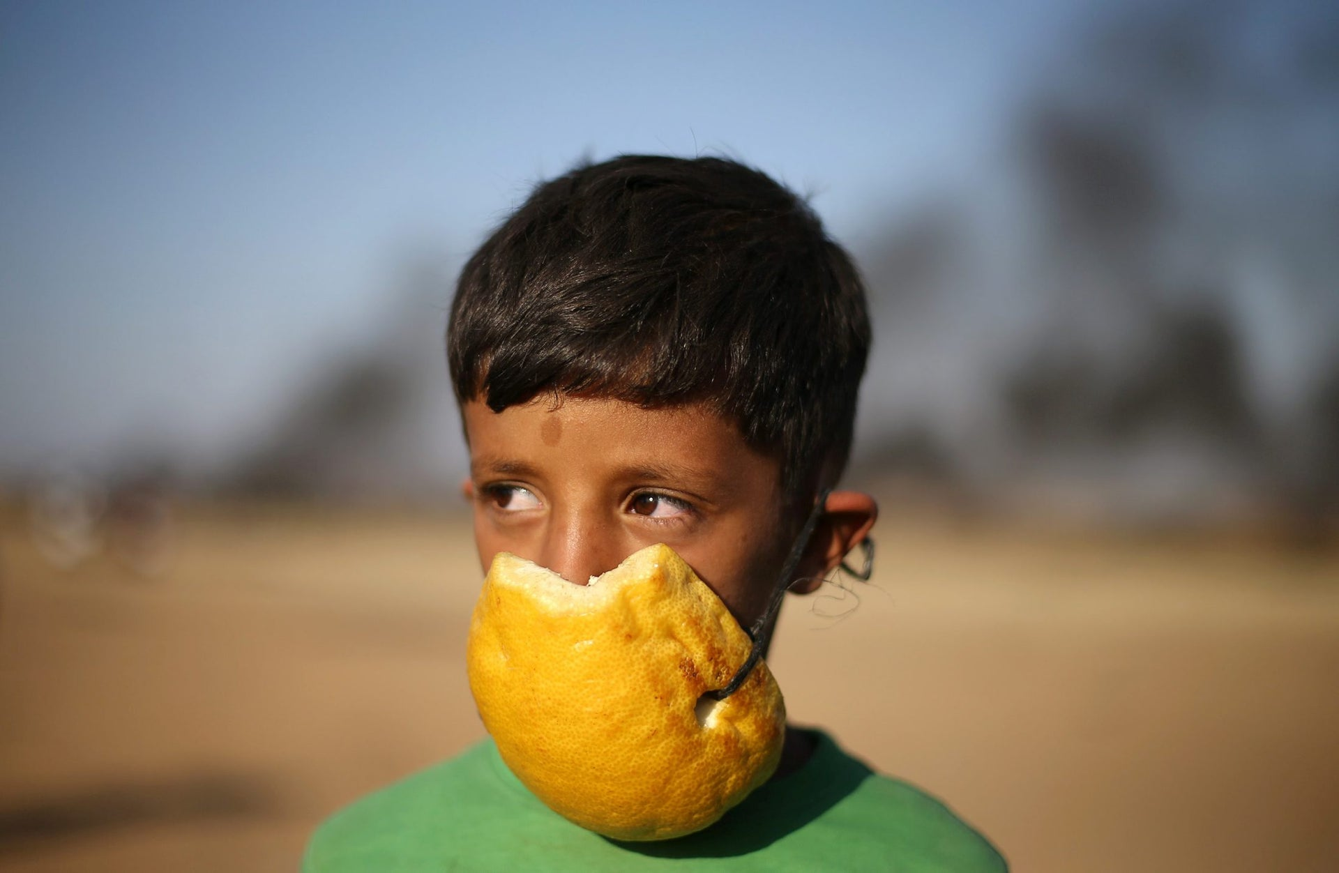 A Palestinian boy covers his nose with part of a pomelo to protect himself from inhaling tear gas fired by Israeli troops during a protest at the Israel-Gaza border in the southern Gaza Strip April 9, 2018. Picture taken April 9, 2018.