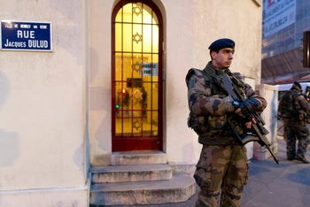 """French soldiers patrol on January 21, 2015 in front of a synagogue in Neuilly-sur-Seine, outside Paris, as part of France's national security alert system Vigipirate. The anti-terrorism Vigipirate plan which has been reinforced in the wake of recent attacks will be maintained in France """"as long"""" as """"risk prevails"""", French Interior minister Bernard Cazeneuve said on January 16."""