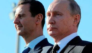 """FILE - This Dec. 11, 2017 file photo, shows Russian President Vladimir Putin, right, and Syrian President Bashar Assad watching troops march at the Hemeimeem air base in Syria. In comments published on the official presidency Telegram channel Wednesday, March 14, 2018, Assad said his country's war on terrorism will continue as long as there is """"a single terrorist"""" on Syrian territories. Russia and Iran have been strong backers of Assad, helping him in his bid to regain control of territories. (Mikhail Klimentyev, Sputnik, Kremlin Pool Photo via AP, File)"""