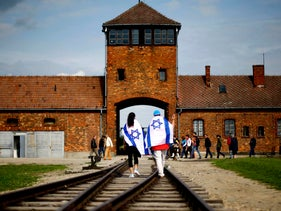 Young visitors with Israeli flags walk on railway tracks on the grounds of the former Nazi death camp of Auschwitz-Birkenau. June 25, 2015