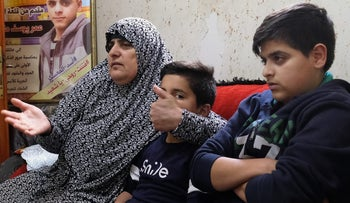 Mahmoud Mahdi (front) with his mother, Na'ama. He was questioned without a lawyer or his parents present, even though he's a minor.