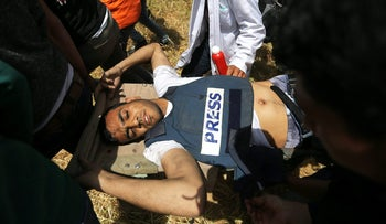 Mortally wounded Palestinian journalist Yaser Murtaja, 31, is evacuated during clashes with Israeli troops at the Israel-Gaza border, April 6, 2018.