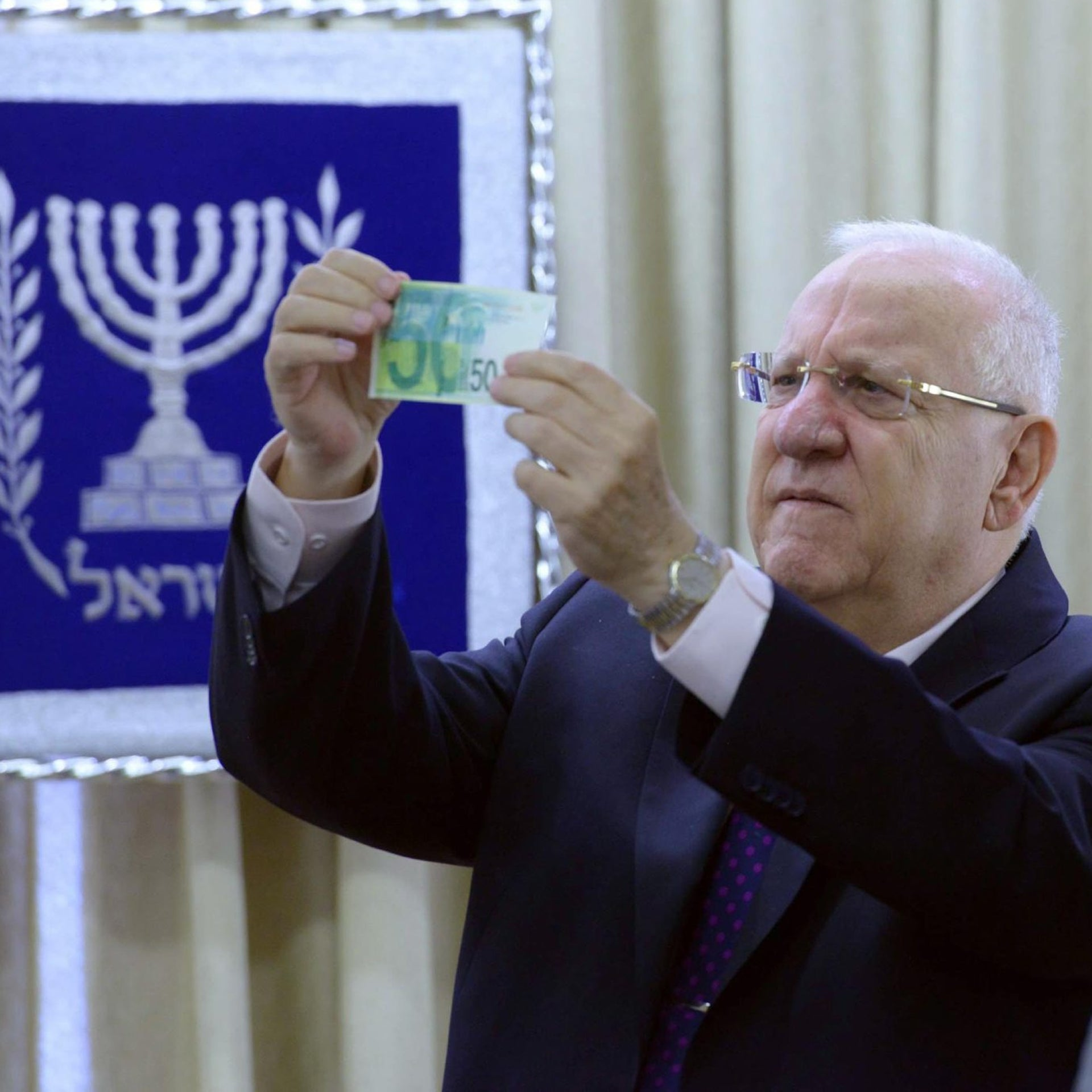 President Reuven Rivlin holds up a 50 shekel banknote.