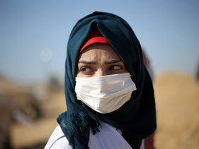 A Palestinian medic wears a mask to protect herself from inhaling tear gas fired by Israeli troops during a protest at the Israel-Gaza border in the southern Gaza Strip April 9, 2018. Picture taken April 9, 2018. REUTERS/Ibraheem Abu Mustafa