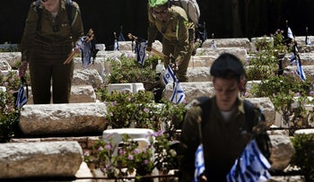 Israeli soldiers place their national flag on graves of killed comrades at Mount Herzl military cemetery in Jerusalem on April 14, 2010, five days before the start of the Israeli Memorial Day for fallen soldiers. Remembrance Day will start on April 18 in the evening and is followed immediately by the 62nd anniversary of the creation of the State of Israel. AFP PHOTO/MENAHEM KAHANA