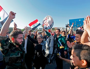 Syrians wave the national flag and portraits of President Bashar Assad in Umayyad Square, Damascus after air strikes by the U.S., Britain and France in the early morning of April 14, 2018.