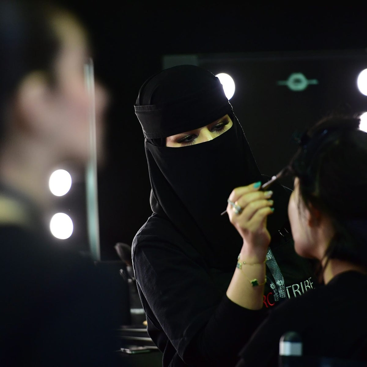 A Saudi makeup artist preps a model backstage during the first Arab Fashion Week in Riyadh on April 13, 2018. Arab Fashion Week is taking place at Riyadh's eco-friendly Apex Centre, a white honeycomb-like venue designed by the late celebrated Iraqi-British architect Zaha Hadid. / AFP PHOTO / GIUSEPPE CACACE