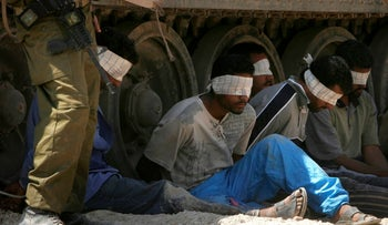 FILE PHOTO: Men sit blindfolded as they are arrested at the Gaza border, 2007