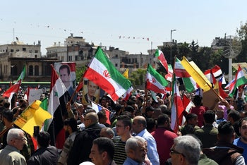 Syrians wave Syrian, Iranian and Hezbollah flags, wave portraits of President Bashar al-Assad as they protest the U.S., French and UK strikes against the Syrian regime. Aleppo, April 14, 2018