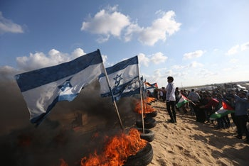 Palestinian protestors prepare to set fire to Israeli flags at protests on the Israel-Gaza border east of Jabalia in the northern Gaza Strip. April 10, 2018