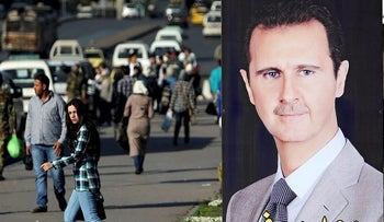 A woman walks near a picture of Syrian President Bashar al Assad in Damascus, Syria April 15, 2018