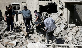 People carry a body on a stretcher in the besieged eastern Ghouta town of Hamouriyeh near Damascus, Syria, February 21, 2018